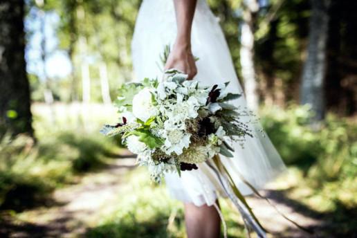 Vit brudklänning och blomsterbukett i skogsmiljö.