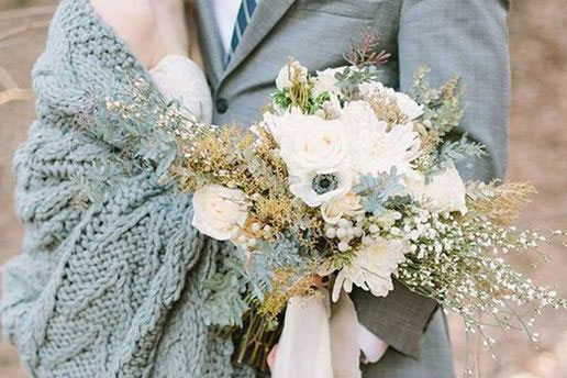 Bröllopspar i grå klädsel med vit blomsterbukett.